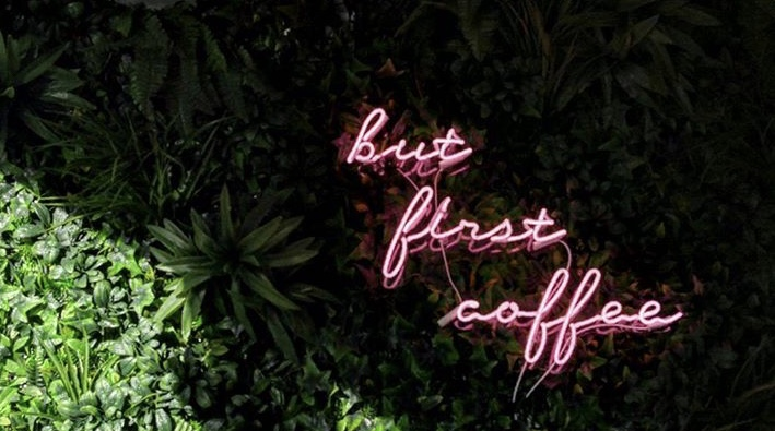 a pink neon sign at blanche bakery in Cardiff says but first coffee