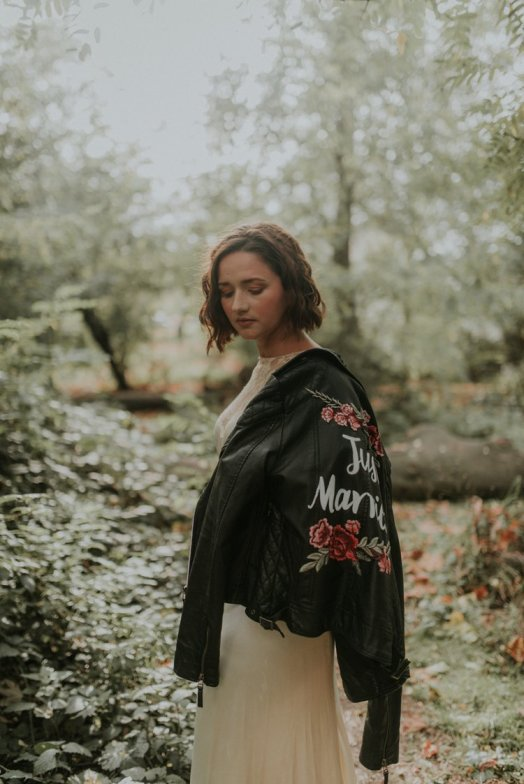 A boho bride poses in a vintage dress and custom jacket by Back Chat Designs on For The Love Of Hygge